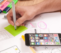 A smartphone on a table with wireframe templates for UX design