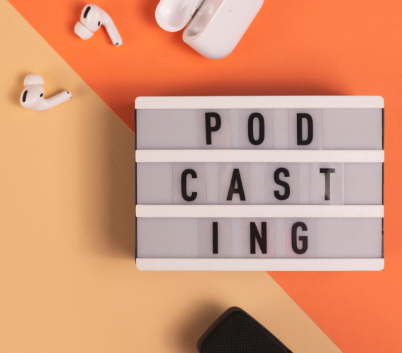 Air Pods, a Microphone and a sign saying Podcasting on an orange background