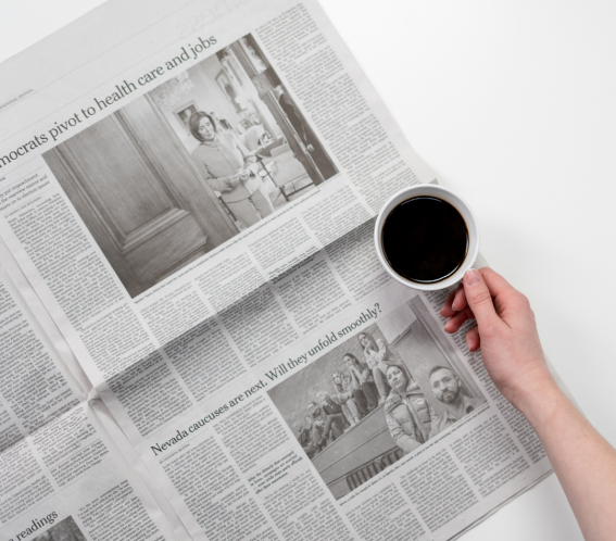 An open newspaper with a coffee Cup