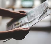 A set of hands holding up a newspaper