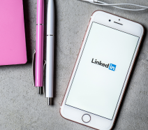 A table with a notebook and pens and a mobile phone that has LinkedIn open